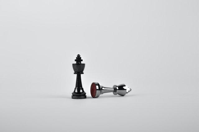 Czarny i srebrny pionek na białym tle. Czarny stoi w pionie a srebrny leży.