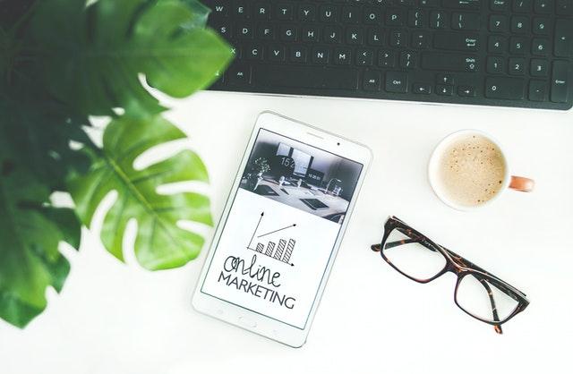 """Stół z klawiaturą, okularami i telefonem, na którym jest napis """"online marketing"""""""