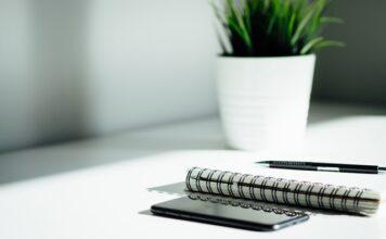 Biurko z zeszytem, telefonem długopisem i kwiatkiem.