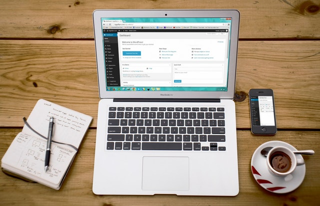 Laptop otwarty na stronie WordPress a obok notatnik i kawa.