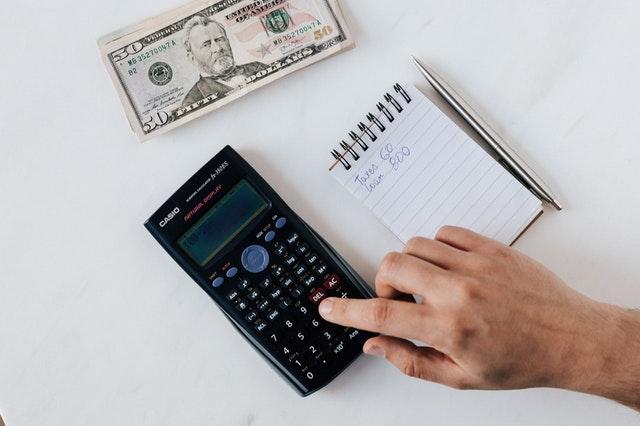 Ręka licząca na kalkulatorze, notes i dolar.