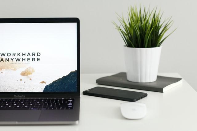 Otwarty komputer, telefon i kwiatek na białym biurku.