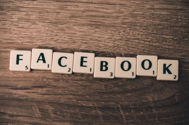 """Napis """"Facebook"""" ułożony z kostek do gry w skruble."""