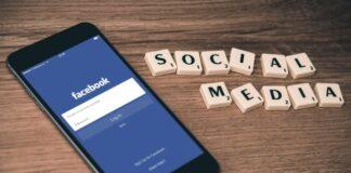 """Telefon komórkowy z włączonym facebookiem, a obok napis """"social media"""""""