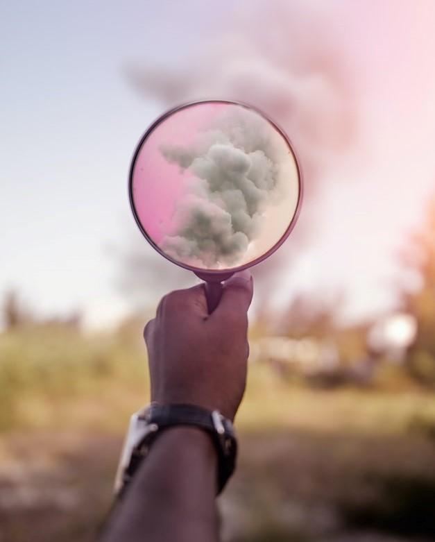 Ręka trzymająca lupę, w której widać powiększone chmury.