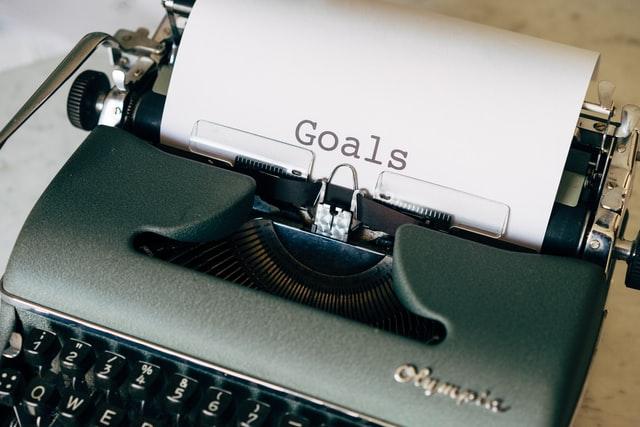 """Maszyna do pisania z kartką, na której jest napis """"goal"""" - cel."""