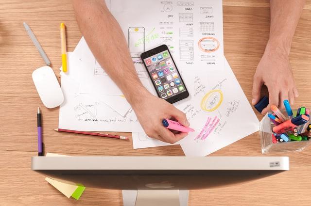 Biurko z kartkami, smartfonem i kolorowymi mazakami.