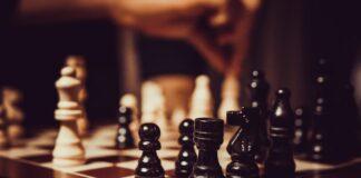 Szachy - białe i czarne figury szachowe na planszy.