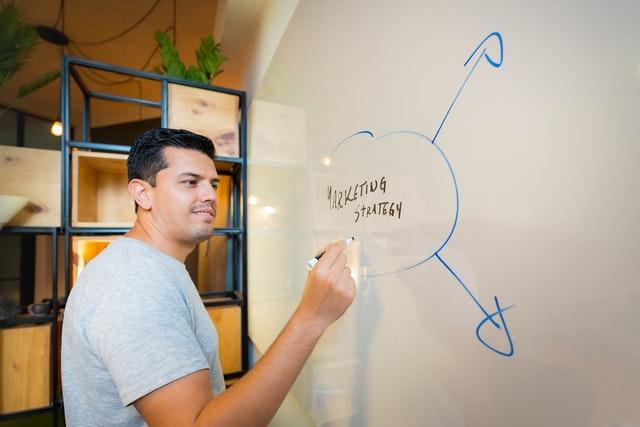 """Mężczyzna piszący po tablicy """"Marketing strategy"""""""