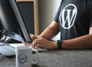 """Mężczyzna siedzący przed komputerem w koszulce z wielkim """"W"""" i kubkiem z napisem WordPress"""