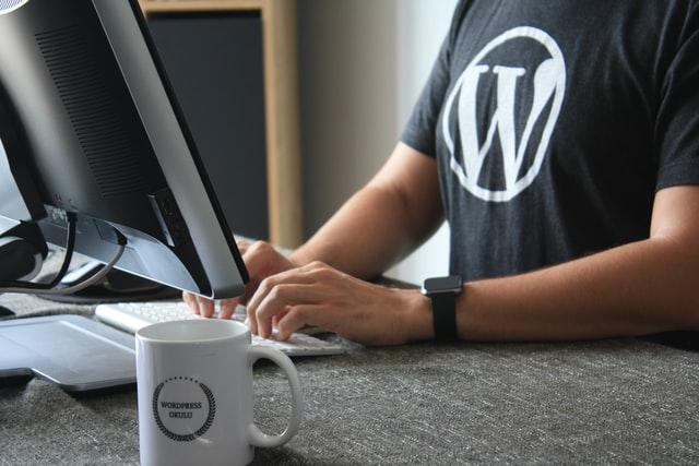 Mężczyzna siedzący przed komputerem w koszulce z wielkim