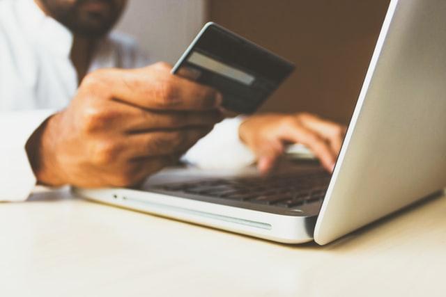Mężczyzna trzymający kartę płatniczą i robiący zakupy przez neta