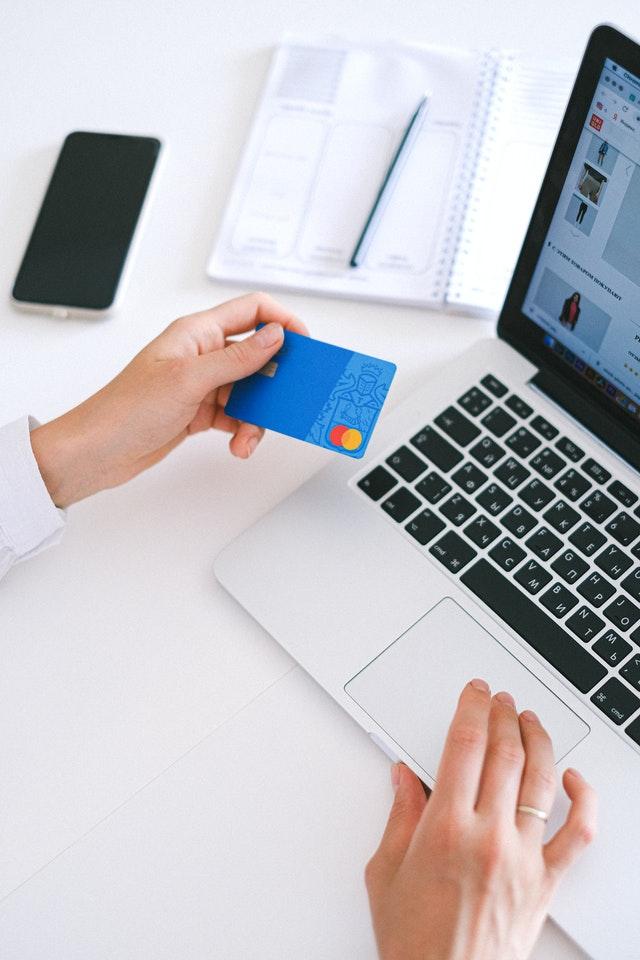Kobieta przed laptopem trzymająca kartę płatniczą, notes i długopis.
