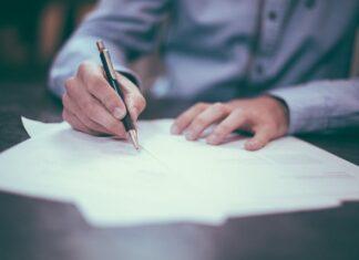 Mężczyzna w koszuli podpisujący dokumenty.