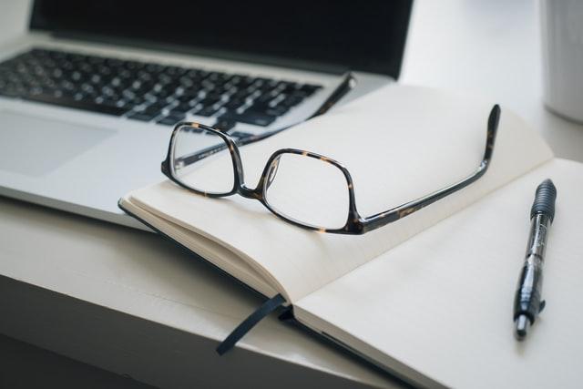 Loptop i ostwarty notes na którym leżą okulary