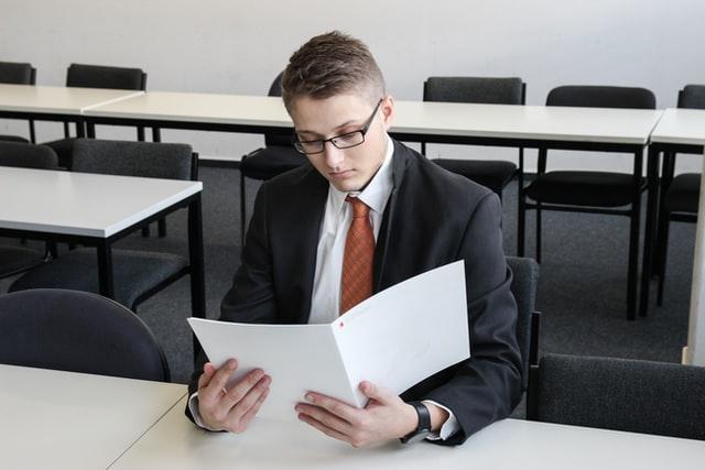 Mężczyzna w garniturze czytający CV.