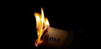 """Płonący papier z napisem """"czas"""" w ciemnym Pokoju"""