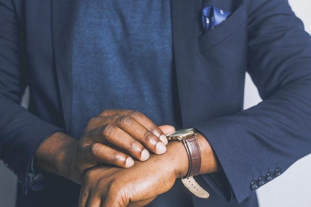 Stojący mężczyzna patrzący za zegarek