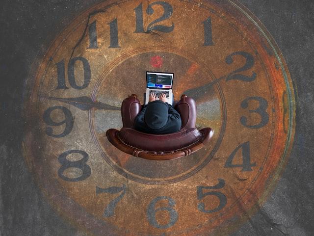 Mężczyzna siedzący w fotelu z laptopem na wielkim zegarze.