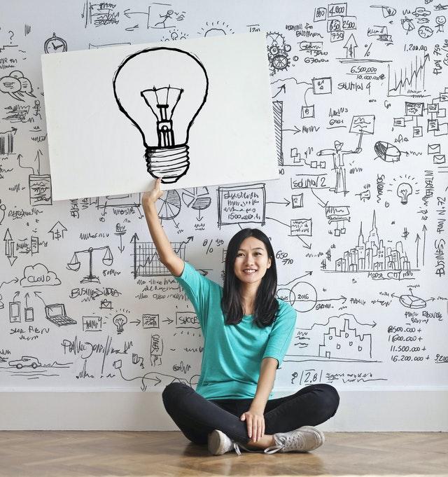Kobieta trzymająca białą tablicę, na której narysowana jest żarówka.