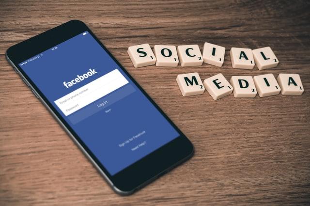 """Telefon z widocznym Facebookiem i napis """"social media"""" z kostek do gry w scrubble."""