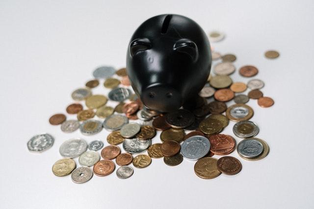 Czarna świnka skarbonka na tle rozrzuconych monet.