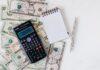 Kalkulator, notes i długopisy leżący na dolarach.