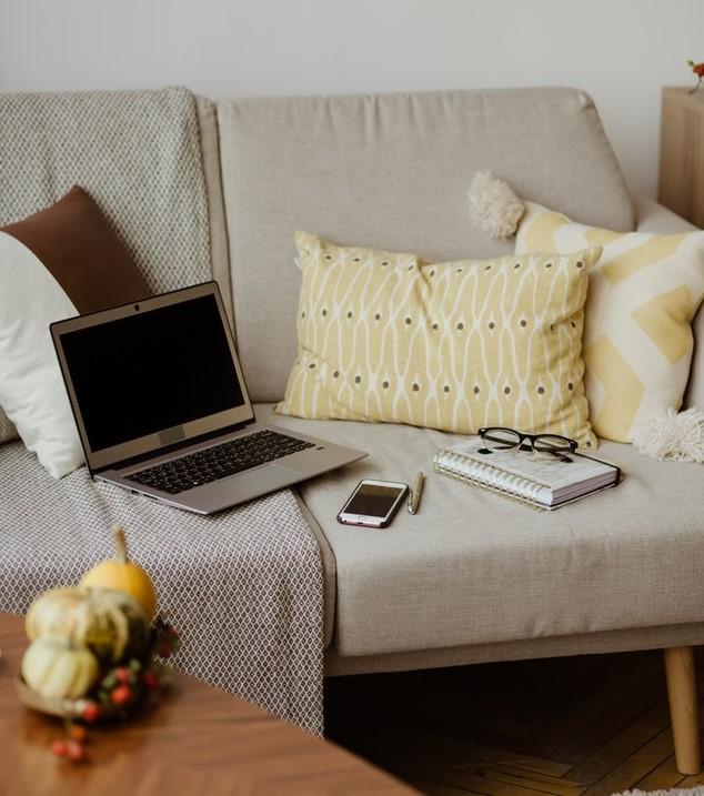 Laptop na kanapie a obok niego smartfon okulary i zeszyt.
