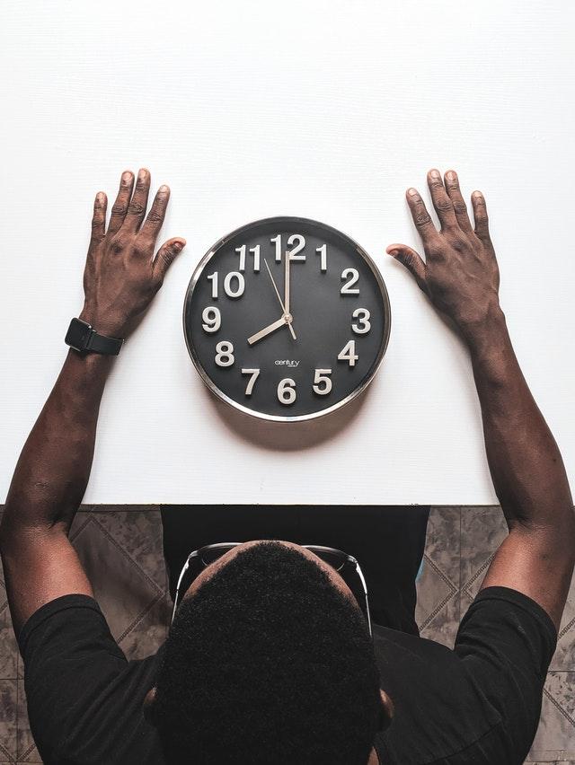 Mężczyzna siedzący przy białym stole na którym leży zegar ścienny
