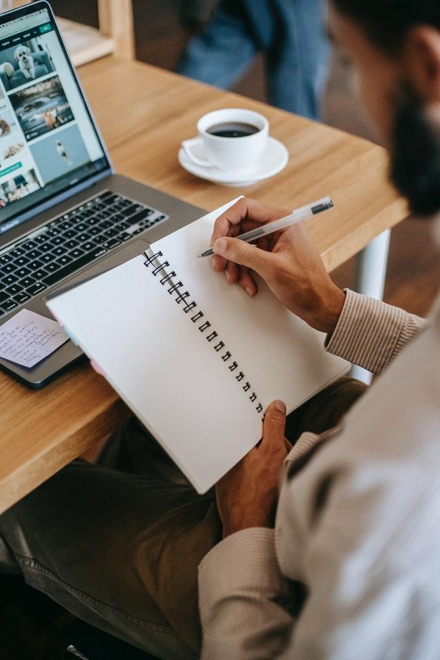 Meżczyzna siedzący przed laptopem, trzymający w ręku zeszyt i długopisy. Robiący notatki.