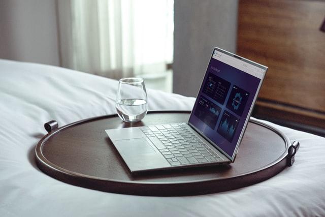 Laptop i szklanka wody na tacy leżącej na łóżku.