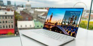 Laptop na biurku przy oknie z pięknym widokiem na miasto.