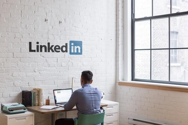 Mężczyzna siedzący przy biurko a na ścianie napis LinkedIn