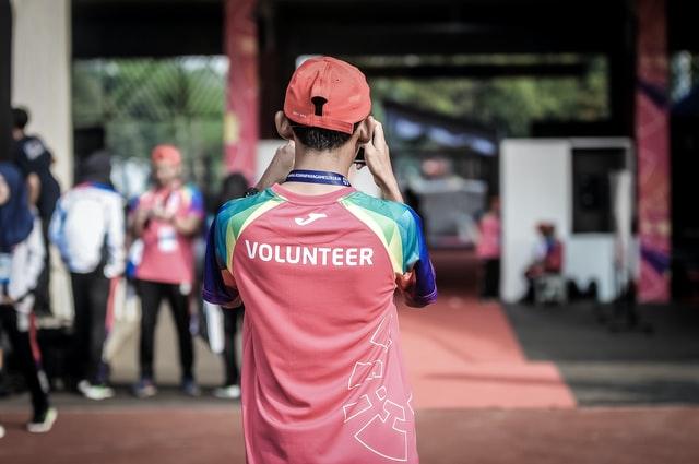 """Mężczyzna z aparatem w koszulce z napisem """"wolontariusz"""""""