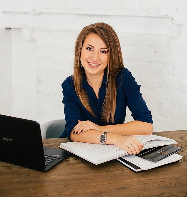 Kobieta manager opierająca się o dokumenty.