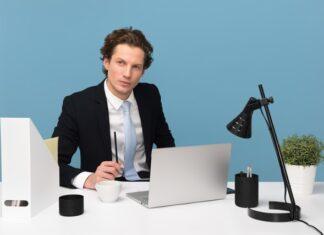 Mężczyzna siedzący przy biurku z laptopem i dokumentami.