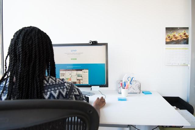 Mężczyzna siedzący przed ekranem komputera, na którym widać Trello