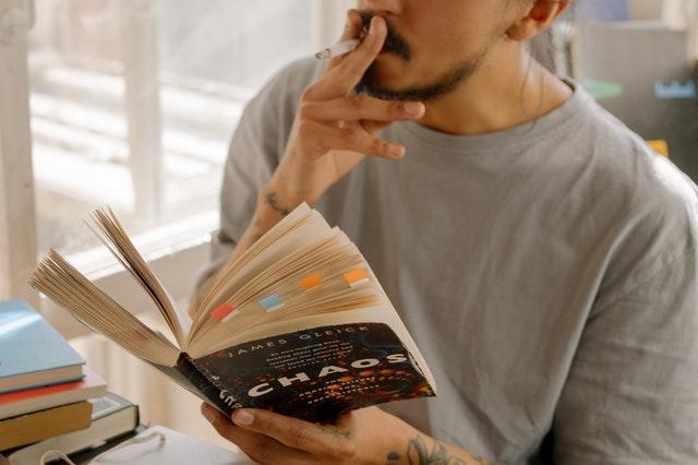 Chłopak czytający podręcznik i palący papierosa.