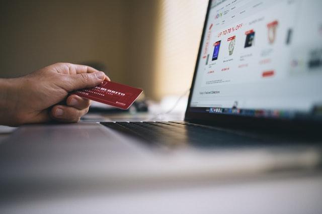 Laptop z wyświetlonym sklepem internetowym i karta płatnicza
