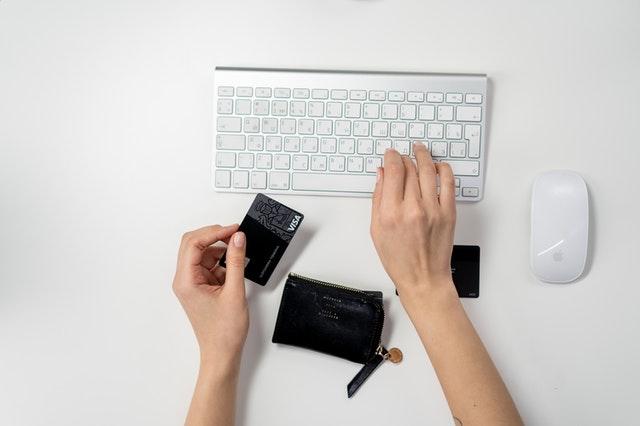 Kobieta trzymająca w ręku kartę i pisząca na klawiaturze.
