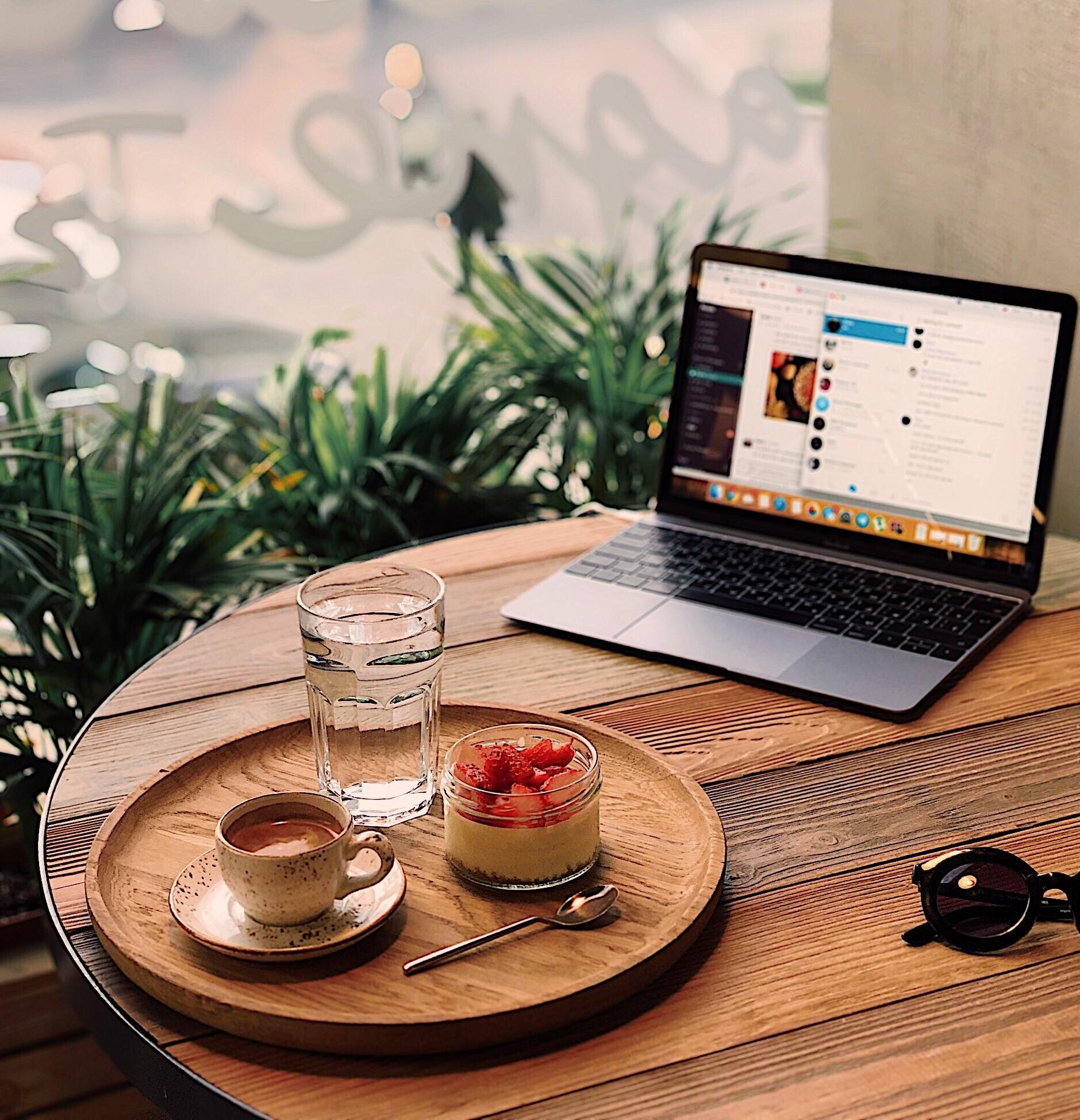 Laptop na stoliku w kawiarni, a obok taca z kawą i deserem.