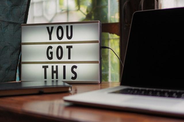 Laptop na biurku i obrazek z napisem