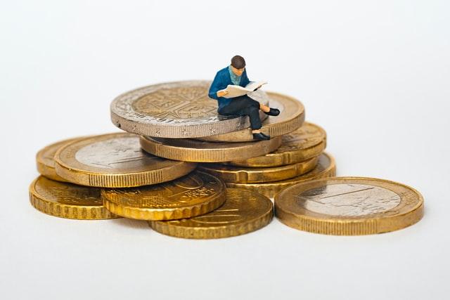 Mężczyzna siedzący na wielkich monetach - oczędności.