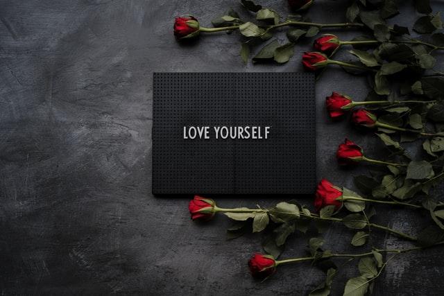 """Napis """"love yourself"""" w otoczeniu róż."""