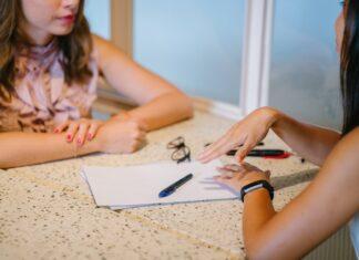 Dwie osoby przy biurku prowadzące rozmowę.