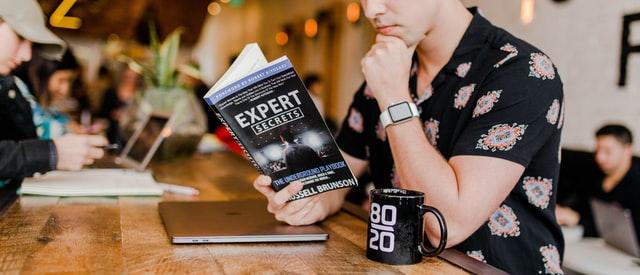 """Mężczyzna czytający książkę """"Ekspert"""""""
