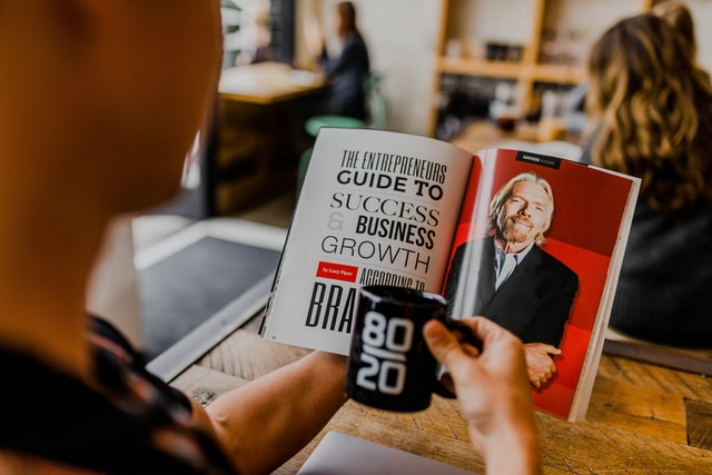 """Mężczyzna czytający gazetę """"Przewodnik do sukcesu i rozwój biznesu"""""""