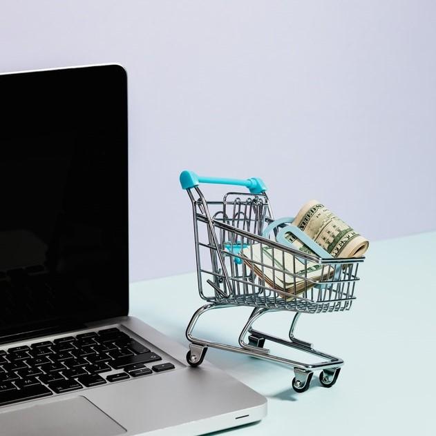 Mały wózek sklepowy z pieniędzmi w środku stojący na laptopie