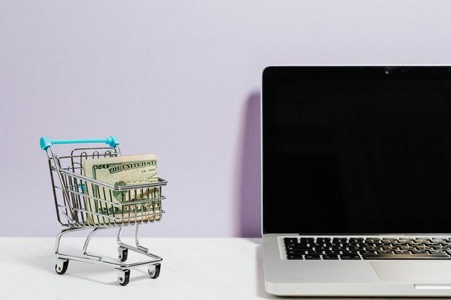 Mały wózek sklepowy z pieniędzmi w środku i laptop