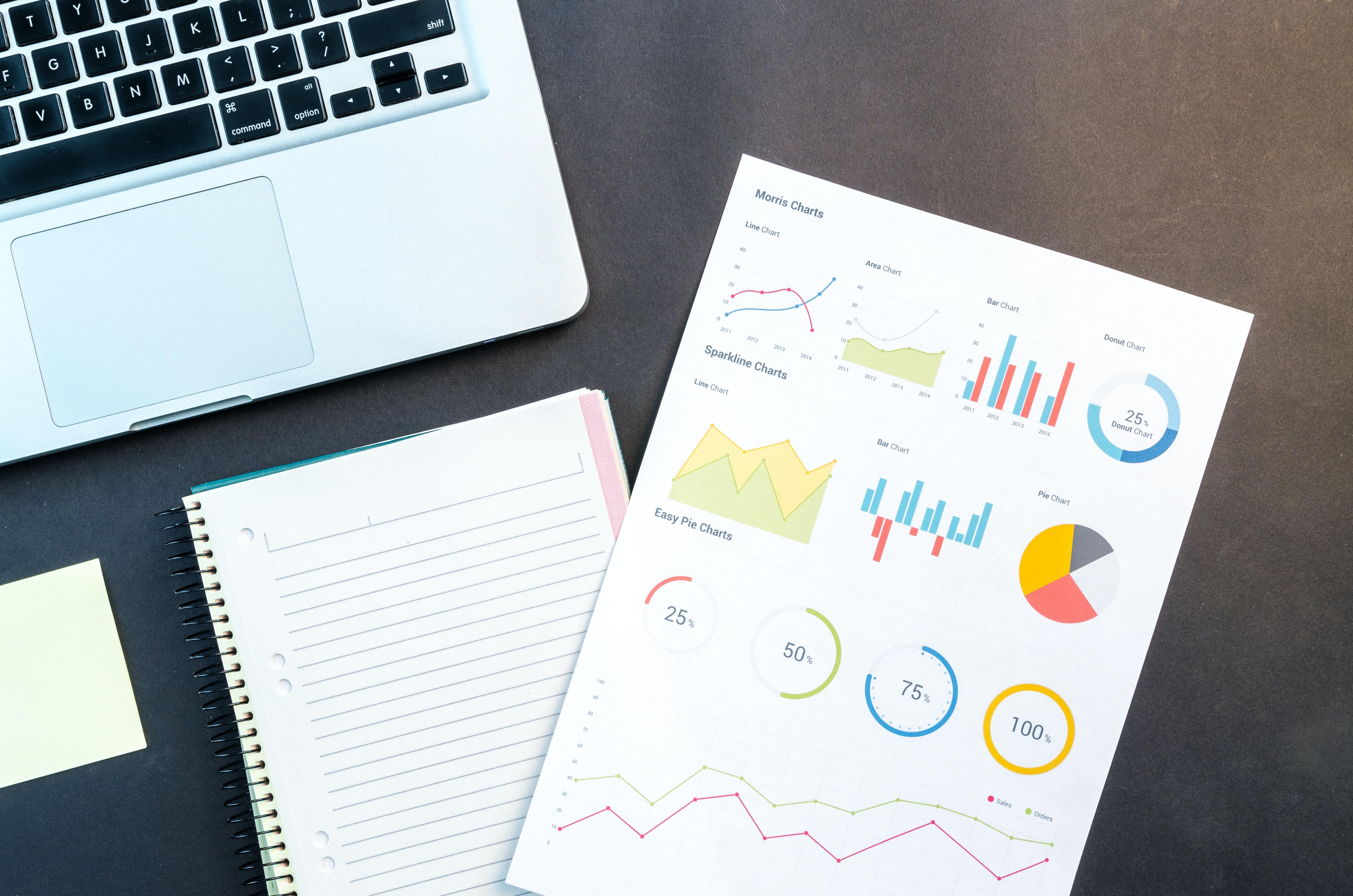 Laptop i wydrukowana kartka z różnymi statystykami